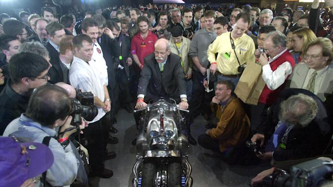 FILE - In this Monday, Jan. 6, 2003, file photo, Chrysler Group President and CEO Dieter Zetsche is surrounded by media as he sits on a Dodge Tomahawk concept motorcycle unveiled at the North American International Auto Show in Detroit. Hundreds of thousands of buyers and car fans are expected to crowd Detroit's North American International Auto Show from Jan. 14-27, 2013. Some 800,000 visitors are expected to descend on the city's 18-acre Cobo Center, where more than 500 cars and trucks will be on display.  (AP Photo/Paul Sancya, File)