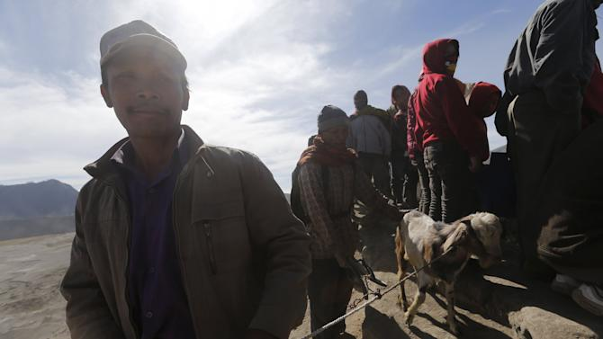 Hindu worshippers hold a goat, which will be thrown into the crater as their offering, during the Kasada Festival at crater of Mount Bromo in Probolinggo