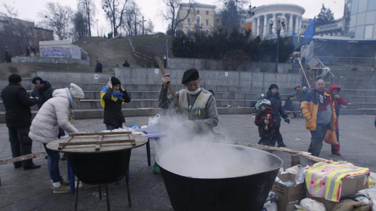 A man cooks at a meal area set up near the Ukrainian cabinet of ministers building, during a rally to support EU integration in Kiev
