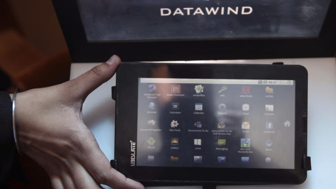 "A DataWind representative displays the supercheap 'Aakash' Tablet computers during its launch in  New Delhi, India, Wednesday, Oct. 5, 2011. The $35 basic touchscreen tablet aimed at students can be used for functions like word processing, web browsing and video conferencing. 'Aakash' , manufactured by DataWind has a 7""Android 2.2 touch screen and a HD video co-processor. The Indian government intends to deliver 10 million tablets to students across India. (AP Photo/Gurinder Osan)"