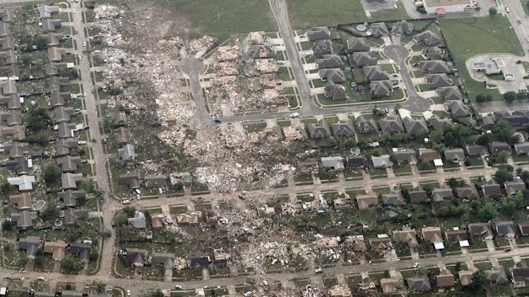 This aerial photo shows the remains of homes hit by a massive tornado in Moore, Okla., Monday May 20, 2013. A tornado roared through the Oklahoma City suburbs Monday, flattening entire neighborhoods, setting buildings on fire and landing a direct blow on an elementary school. (AP Photo/Steve Gooch)