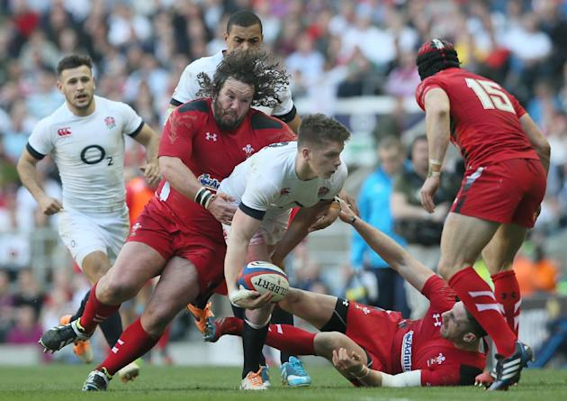 England's Owen Farrell goes to pass the ball as he is tackled by Wales's Adam Jones, left, during the Six Nations Rugby Union match between England and Wales at Twickenham stadium in London Su