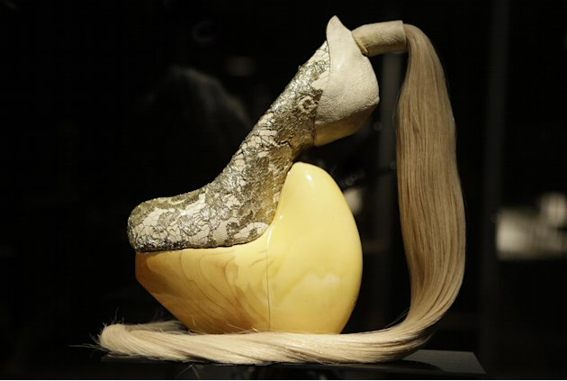 "This Feb. 11, 2013 photo shows a shoe, designed by Masaya Kushino, and made with lacquered Japanese cypress wood, human hair, and lace, displayed at the ""Shoe Obsession"" exhibit at The Museum at the F"
