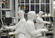 Renesas employees work at the company&#39;s Naka wafer fabrication factory in Ibaraki prefecture. Shares in troubled Japanese microchip maker Renesas rocketed 35 percent Wednesday following reports that a major US investment fund plans to spend $1.3 billion to take control of it