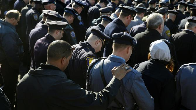 Police hold bow their heads in silence as they listen to the funeral service for slain NYPD officer Ramos outside the Christ Tabernacle Church in the Queens borough of New York