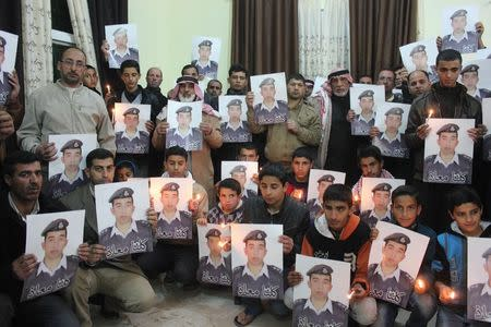 Relatives of Islamic State captive Jordanian pilot Muath al-Kasaesbeh hold his portrait as they take part in a rally in his support at the family's headquarters in the city of Karak