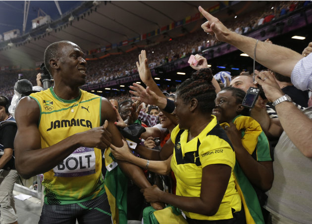 Jamaica's Usain Bolt, left, celebrates winning the gold medal in the men's 200-meter final during the athletics in the Olympic Stadium at the 2012 Summer Olympics, London, Thursday, Aug. 9, 2012. (AP