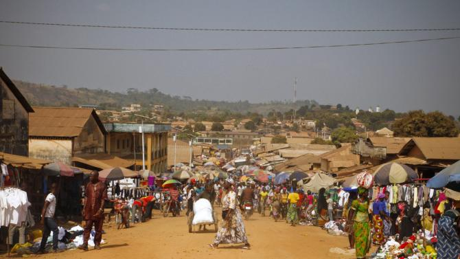 People walk at the main market in Gueckedou