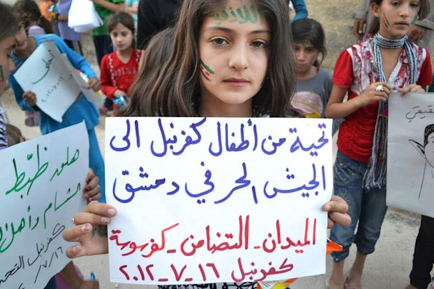 "In this citizen journalism image taken on Monday, July 16, 2012 and provided by Edlib News Network ENN, a Syrian girl holds a poster with Arabic that reads, ""greetings from Kfarnebel's children to the Free Syrian Army soldiers in Damascus,"" during a demonstration in Kfarnebel, Idlib province, northern Syria. Syrian rebels have launched an offensive to ""liberate"" the country's largest city of Aleppo, an opposition commander said Sunday, while in Damascus government troops backed by helicopter gunships wrested back control of rebel-held neighborhoods. (AP Photo/Edlib News Network ENN) THE ASSOCIATED PRESS IS UNABLE TO INDEPENDENTLY VERIFY THE AUTHENTICITY, CONTENT, LOCATION OR DATE OF THIS HANDOUT PHOTO"