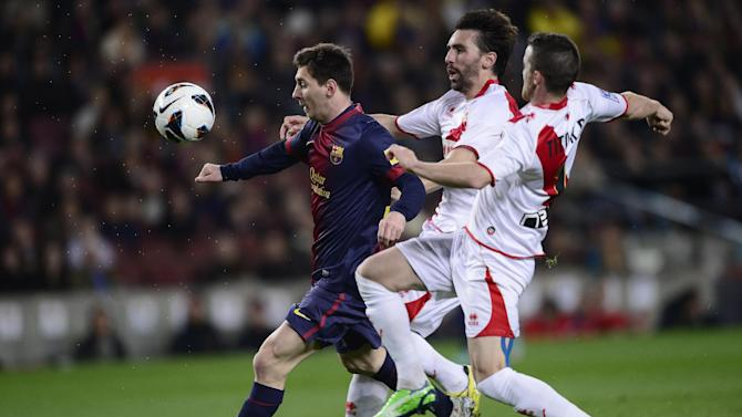 FC Barcelona's Lionel Messi from Argentina, left, duels for the ball against Rayo Vallecano's Tito, right, during a Spanish La Liga soccer match at the Camp Nou stadium in Barcelona, Spain, Sunday, March 17, 2013. (AP Photo/Manu Fernandez)