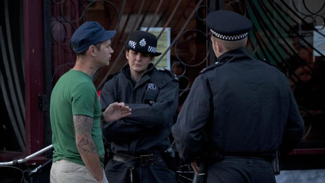 Police officers question a man during a routine stop and search operation on Wednesday, Aug. 10, 2011 in Hackney, North London. An eerie calm prevailed over most of London as night fell Wednesday, with a highly-visible police presence throughout the city. (AP Photo/Karel Prinsloo)