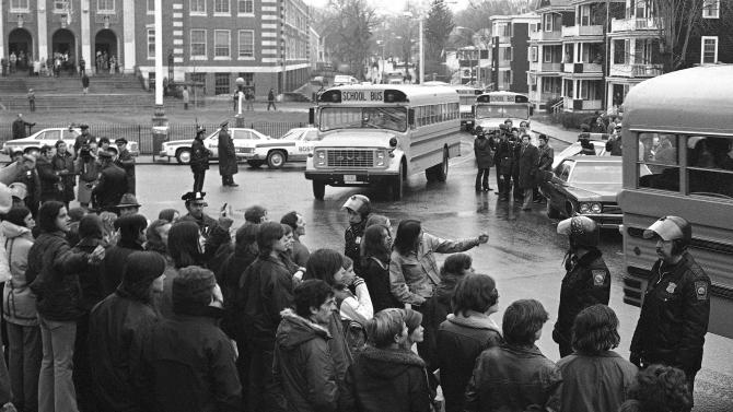 In this Dec. 12, 1974 file photo, white students, who walked out of Boston's Hyde Park High School, stand along the curb and jeer school buses carrying blacks home from the school. The nonprofit Union of Minority Neighborhoods is hosting group exercises across Boston in 2013, where participants talk about how the city's busing crisis impacted them in the 1970s. Organizers hope it will unite people to fight for better access to quality public schools for all students, even as another new Boston school assignment system starts. (AP Photo/Frank C. Curtin, File)