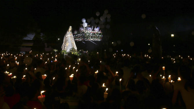 "Filipino devotees hold candles during the traditional Easter Sunday ritual of the meeting of the ""Risen Christ"" and ""Mother Mary"" held at dawn at the Santo Domingo church in suburban Quezon city, north of Manila, Philippines, Sunday, March 31, 2013. The event culminates the observance of Holy Week in this predominantly Roman Catholic nation. (AP Photo/Aaron Favila)"