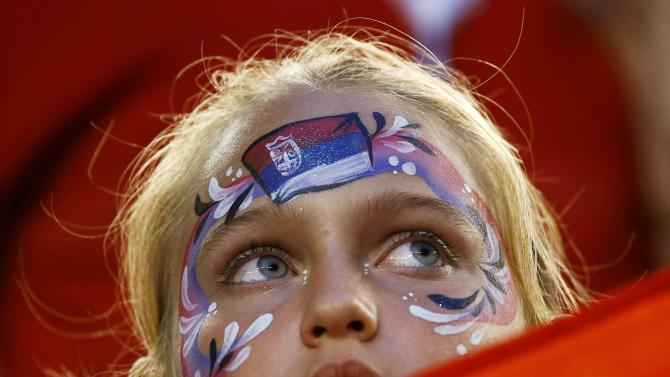 A supporter of Novak Djokovic of Serbia with her face painted watches his men's singles quarter-final match against Milos Raonic of Canada at the Australian Open 2015 tennis tournament in Melbourne