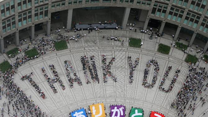 """People spell out the words """"THANK YOU"""" in Tokyo on September 8, 2013, after the Japanese city won the right to host the 2020 Olympics"""