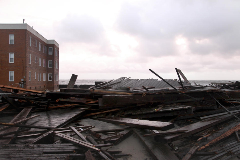 Large chunks of the boardwalk are piled near an apartment building on the ocean in Atlantic City, N.J., Tuesday, Oct. 30, 2012. Sandy, the storm that made landfall Monday, caused multiple fatalities, halted mass transit and cut power to more than 6 million homes and businesses.  (AP Photo/Seth Wenig)