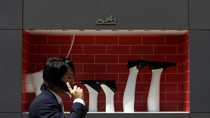 A man on his phone walks past a display window outside a luxury department store in Tokyo