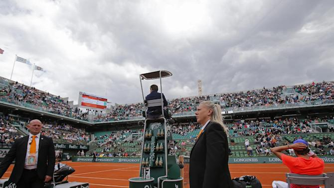 Two security guards keep an eye on the spectators as Lucas Pouille of France, right, takes a break between games in the first round match of the French Open tennis tournament against compatriot Gilles Simon at the Roland Garros stadium, in Paris, France, Monday, May 25, 2015. On Sunday a fan ran onto the court to take a selfie with Swiss Roger Federer at the end of his first round match. (AP Photo/Christophe Ena)
