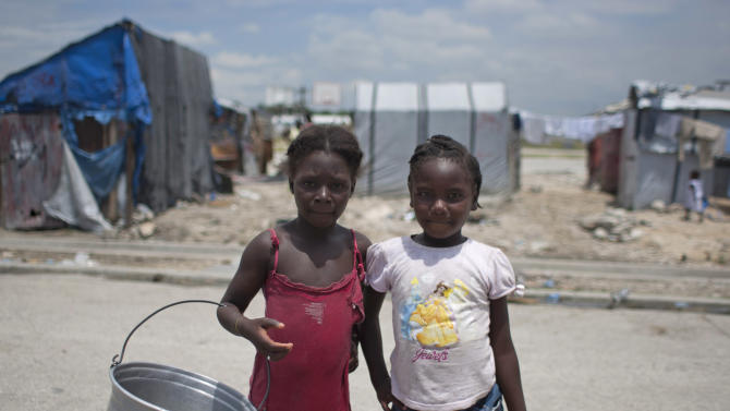 Alix Milanda, 9, left, poses for a picture with her friend Shella St-Telise, 9, as they look for water at the Jean-Marie Vincent camp for people displaced by the 2010 earthquake, in Port-au-Prince, Haiti, Monday, April 22, 2013. The post-quake encampments became symbolic of the widespread devastation caused by the January 2010 earthquake, which toppled thousands of buildings and killed more than 300,000 people. The number of people still living in camps has become a barometer of the success or failure of how to house Haitians, though it's unclear what happens to most people after they leave the formal camps. (AP Photo/Dieu Nalio Chery)
