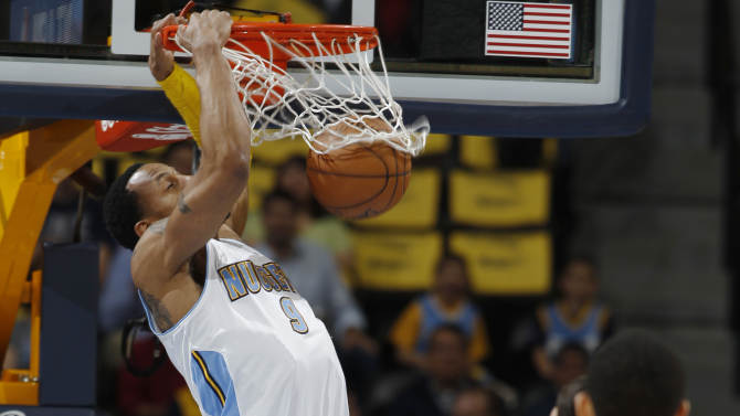 Denver Nuggets guard Andre Iguodala hangs from the rim after dunking against the Golden State Warriors during the first quarter of Game 5 of their first-round NBA basketball playoff series, Tuesday, April 30, 2013, in Denver. (AP Photo/David Zalubowski)
