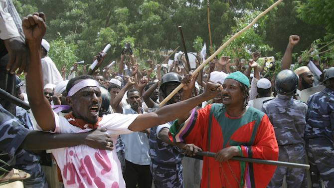 A Sudanese protester chants slogans as a cordon of police try to contain the crowd during a protest in Khartoum, Sudan, Friday, Sept. 14, 2012, as part of widespread anger across the Muslim world about a film ridiculing Islam's Prophet Muhammad. Germany's Foreign Minister says the country's embassy in the Sudanese capital of Khartoum has been stormed by protesters and set partially on fire. Minister Guido Westerwelle told reporters that the demonstrators are apparently protesting against an anti-Islam film produced in the United States that denigrates the Prophet Muhammad.(AP Photo/Abd Raouf)