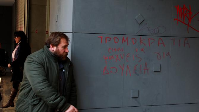 People leave an office of Labor Force Employment Organization (OAED) with a graffiti reads in Greek ''Terrorism = Job Seeking'' in central Athens, Thursday, Jan. 10, 2013. Unemployment has reached new highs in Greece, with October 2012 figures showing the jobless rate at 26.8 percent, a major increase from the same month in 2011. (AP Photo/Thanassis Stavrakis)