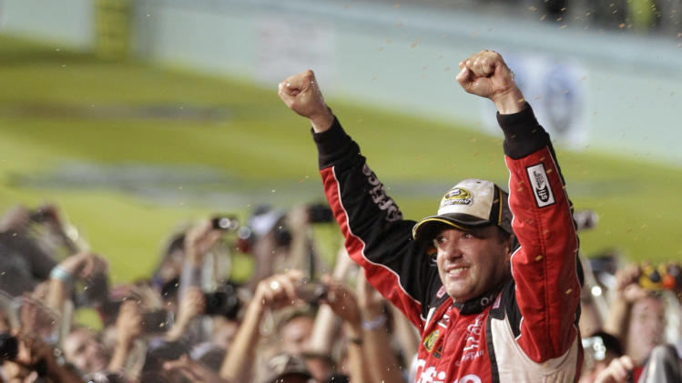 Tony Stewart celebrates after winning the NASCAR Sprint Cup Series auto race and clinching the series championship, at Homestead-Miami Speedway in Homestead, Fla., Sunday, Nov. 20, 2011. (AP Photo/Chuck Burton)