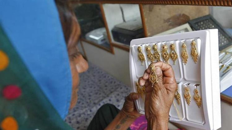 Farmer Bachiben Kolipatle, 63, selects gold earrings inside a jewellery shop at Vadnagar village in Gujarat September 3, 2013. REUTERS/Amit Dave