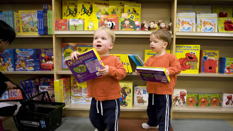 FILE - In this file photo of June 19, 2009, twins Daniel, left, and Thomas O'Brien, 2, look at books at a Barnes & Noble in New York. The number of twins born in the U.S. has soared over the last three decades. (AP Photo/Mark Lennihan, File)