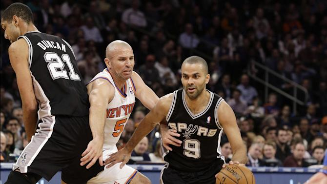 New York Knicks guard Jason Kidd (5) is sandwiched between San Antonio Spurs forward Tim Duncan (21) and guard Tony Parker (9) as Parker drives to the basket in the first half of their NBA basketball game at Madison Square Garden in New York, Thursday, Jan. 3, 2013. (AP Photo/Kathy Willens)