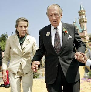 FILE - In this July 17, 2005 file photo, Diane Disney Miller, left, assists Art Linkletter, who fifty years earlier hosted the live opening day telecast of Disneyland, as they depart the podium following a re-dedication ceremony in Anaheim, Calif. Disney Miller, the daughter of Walt Disney and one of his inspirations for building the Disneyland theme park, has died at her home in Napa, California. She was 79. (AP Photo/Ric Francis, File)