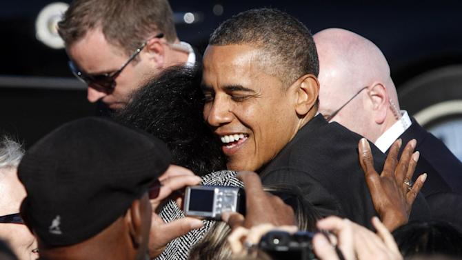 President Barack Obama hugs a supporter at  Rickenbacker International Airport in Columbus, Ohio, as he arrives for a campaign stop at The Ohio State University Tuesday, Oct. 9, 2012. (AP Photo/Paul Vernon)