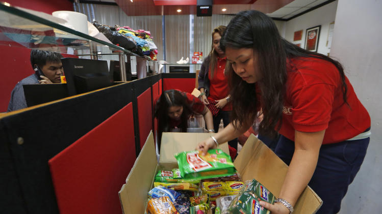 In this Wednesday, Nov. 13, 2013 photo, Filipino staff members pack boxes of donations from overseas workers at an express company in a Hong Kong shopping mall as the relief goods will be shipped to the survivors of Typhoon Haiyan in the Philippines. They gather in California churches, in Hong Kong shopping malls, at prayer vigils in Bahrain and on hastily launched Facebook pages. Philippine overseas workers, cut off from home after a super-typhoon killed more than 2,000 people, are coming together to pray, swap information and launch aid drives. (AP Photo/Kin Cheung)
