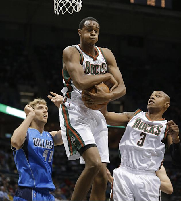 Milwaukee Bucks' John Henson, center, grabs a rebound against Dallas Mavericks' Dirk Nowitzki, left, as Bucks' Caron Butler (3) watches during the first half of an NBA basketball game Saturday, Nov. 9