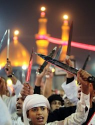 <p>Shiite Muslims raise their swords outside the shrine of Imam Abbas in Karbala on Sunday. Provincial governor Amal al-Din al-Har told AFP that about three million pilgrims, including 200,000 from foreign countries, have come to Karbala for the rituals.</p>