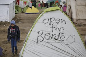 Migrant child walks past a tent at the northern Greek …
