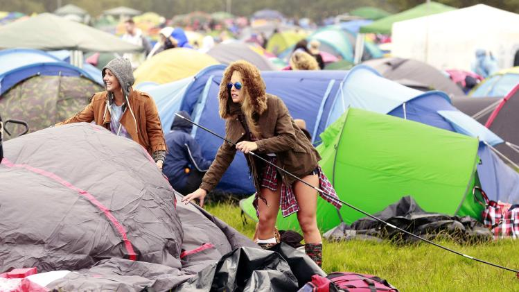 A festival-goer erects her tent on the first day of the Electric Picnic music festival at Stradbally Hall in County Laois