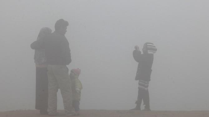 Girl takes a picture of her family on a foggy day in Lahore