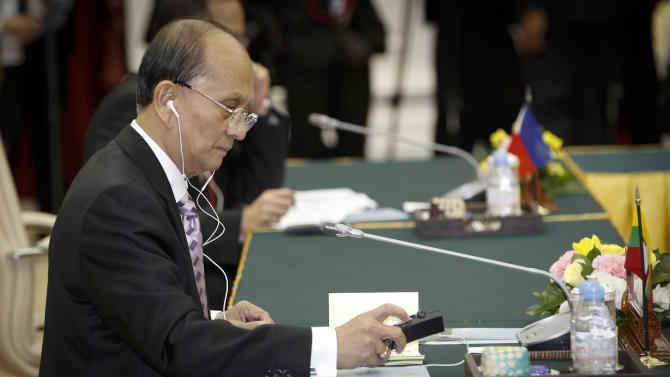 Myanmar's President Thein Sein adjusts his earphone volume during Retreat session of the ASEAN Summit in Phnom Penh, Cambodia, Sunday, Nov. 18, 2012. (AP Photo/Vincent Thian)
