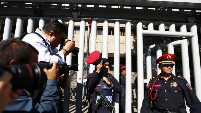 Photographers take pictures of police officers standing at the entrance of the building housing the Assistant Attorney General's Office for Special Investigations on Organized Crime in Mexico City