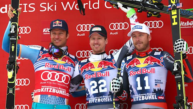 From left second placed Aksel Lund Svindal, of Norway, first placed Hannes Reichel, of Austria, and third placed Bode Miller, of United States, celebrate on the podium at the end of an alpine ski men's World Cup Downhill in Kitzbuehel, Austria, Saturday, Jan. 25, 2014. (AP Photo/Giovanni Auletta)