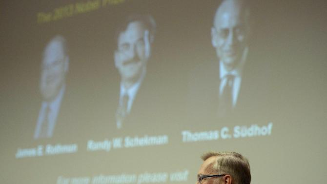 Images of James Rothman and Randy Schekman, of the United States, and German-born researcher Thomas Sudhof are projected on a screen, in Stockholm, Sweden, Monday, Oct. 7, 2013, as Karolinska Institute Nobel committee chairman Goran Hansson announces them as the winners of the 2013 Nobel Prize in medicine. Rothman, Schekman and Sudhof won the 2013 Nobel Prize in medicine on Monday for discoveries on how proteins and other materials are transported within cells. (AP Photo/ TT News Agency Janerik Henriksson) SWEDEN OUT