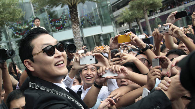 """FILE - In this Nov. 28, 2012 file photo, South Korean rapper PSY, who sings the popular """"Gangnam Style,"""" greets Thai fans after a press conference in Bangkok, Thailand. As """"Gangnam Style"""" gallops toward 1 billion views on YouTube, the first Asian pop artist to capture a massive global audience has gotten richer click by click. So too has his agent and his grandmother. But the money from music sales isn't flowing in from the rapper's homeland South Korea or elsewhere in Asia. With one song, 34-year-old Park Jae-sang — better known as PSY — is set to become a millionaire from YouTube ads and iTunes downloads, underlining a shift in how money is being made in the music business. (AP Photo/Sakchai Lalit, File)"""