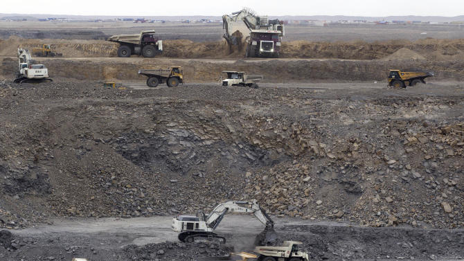 In this July 6, 2012 photo, excavation continues at the Erdenes Tavan Tolgoi coal mining facility in southern Mongolia. Fully 90 percent of Mongolia's exports - coal, copper, cashmere and livestock - go to China, which in turn sends machinery, appliances and other consumer goods that account for a third of Mongolian imports. The rising trade with China now amounts to three-fourths of Mongolia's economy, one of the highest ratios in the world, according to an Associated Press analysis of IMF trade data. (AP Photo/Andy Wong)