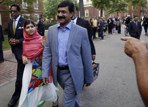 Malala Yousafzai waves to onlookers as she walks with …