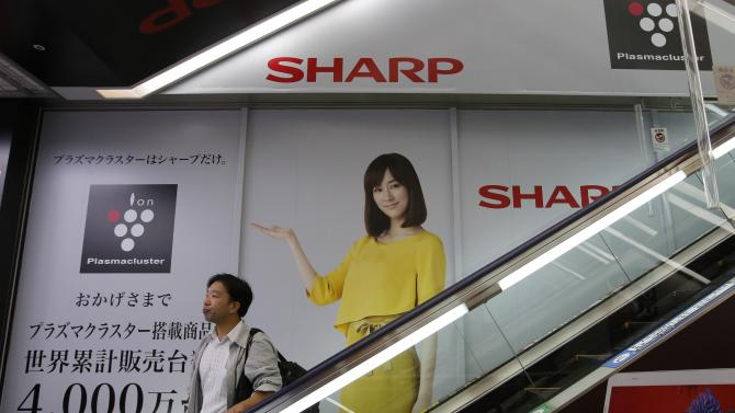 File photo of a man riding an escalator past Sharp Corp's advertisements at an electronics retail store in Tokyo