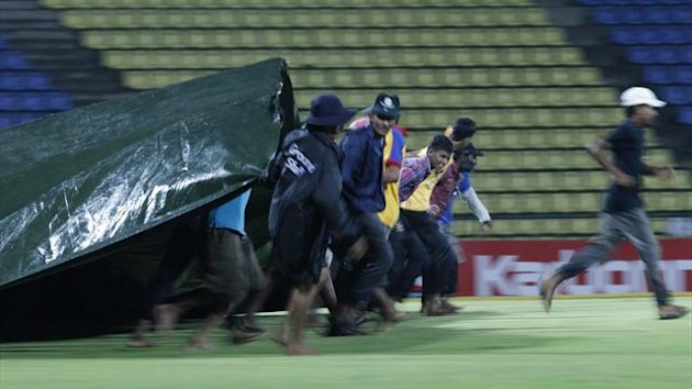 Workers pull the cover over the field as match stopped due to rain during the Twenty20 cricket match between Sri Lanka and New Zealand in Pallekele October 30, 2012