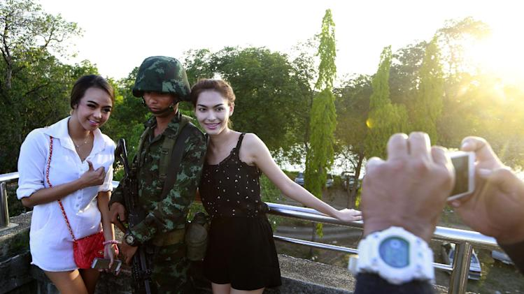 "FILE - In this Tuesday, May 20, 2014 file photo, passersby have their photograph taken with a Thai soldier guarding a pedestrian overfly near the site where pro-government demonstrators stage a rally on the outskirts of Bangkok, Thailand. Thailand's turquoise waters, white-sand beaches, serene Buddhist temples and piquant nightlife have made it one of the world's top tourist destinations. Even in times of crisis, it lives up to its nickname, ""The Land of Smiles."" Martial law Thai-style means tourists can take home souvenir selfies with smiling soldiers. (AP Photo/Wason Wanichakorn, File)"