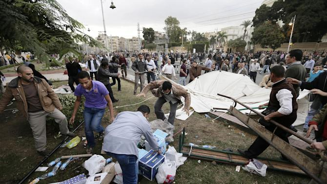 Supporters of Egyptian President Mohammed Morsi remove tents of opposition protesters outside the presidential palace, in Cairo, Egypt, Wednesday, Dec. 5, 2012. Supporters of Morsi and opponents clashed outside the presidential palace. Wednesday's clashes began when thousands of Islamist supporters of Morsi descended on the area around the palace where some 300 of his opponents were staging a sit-in. (AP Photo/Hassan Ammar)