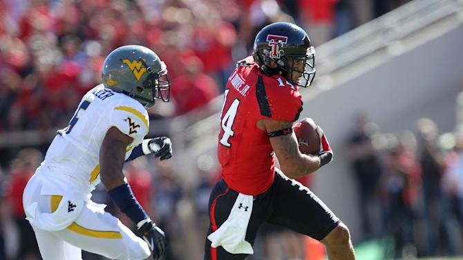 Texas Tech's Darrin Moore gets away from West Virginia's Pat Miller during an NCAA college football game in Lubbock, Texas, Saturday, Oct. 13, 2012. (AP Photo/Lubbock Avalanche-Journal, Stephen Spillman) LOCAL TV OUT